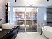 Moderner Waschtisch und freistehende Badewanne vor integrierter Ankleide mit geschlossenen Glasschiebetüren