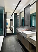 Washstand and base cabinet in spacious bathroom with dark-grey tiles on floor and walls