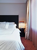Double bed with white bedclothes next to bedside table with retro lamp