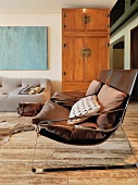 Leather-covered armchair and cushions in front of simple, Oriental-style wooden cupboard