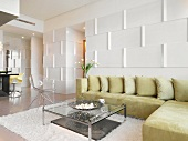 Elegant designer interior with corner sofa against wall with 3D structured surface