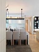 Gepolsterte Stühle am Esstisch unter Ablage mit Kerzen von der Decke abgehängt in offenem Wohnraum