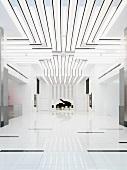 Weisser minimalistischer Raum mit Lichtbändern an Decke und Blick auf Klavierflügel