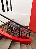 Helical stairwell with red inner stringer and black-painted banister