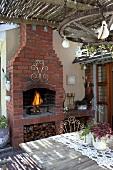 Blick über Holztisch auf Feuer im geziegelten Aussenkamin einer überdachten Terrasse