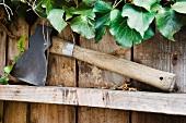 Hatchet Resting on Wood Fence