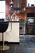 Eine Küche mit Kücheninsel und Edelstahlfronten
