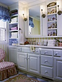 Nostalgic bathroom with white fitted furniture, integrated mirror, shelves of Chinese porcelain and long washstand