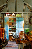 Pastel-coloured, vintage wooden cupboard, gardening utensils and plant pots inside garden shed