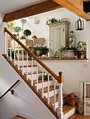 Treppenaufgang in einem Landhaus mit Ablage und Schränkchen für Gartendeko und Gartenutensilien