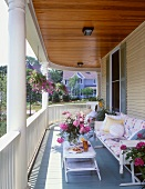 Comfortable furniture, potted plants and opulent bouquet of peonies on curved, summery balcony of house with wooden facade