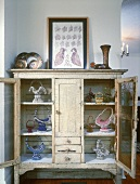 Vintage display cabinet with collection of baskets and framed picture of birds