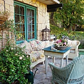 Garden terrace of stone house with vintage furniture and decorative flower arrangement in basket