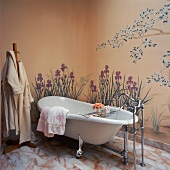 Free-standing bathtub against wall painted with garden flowers