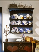 Rustic crockery shelf with collection of plates and pots, collection of baskets on top and antique wooden trunk painted with date and hearts