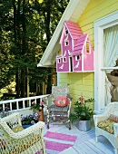 Terrace with yellow house facade, pink nesting box, pink and white striped rug and rustic wooden chair in corner