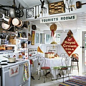 Kitchenette with corner window, round dining table, delicate metal chairs, old-fashioned cooker and colourful collection of signs