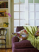 Corduroy sofa with floral cushions and fringed throw: screened French windows in background