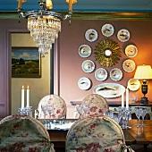 Vergoldeter Sonnenspiegel mit kreisender Porzellansammlung; davor ein Kronleuchter und ein gedeckter Esstisch mit Kerzendeko und Stühle mit Hussen