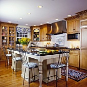 Traditional kitchen with island created to look like dining table and chair-backed bar stools at the counter