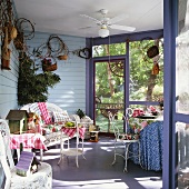 Glazed veranda with wicker furniture and ceiling fan; patterned textiles create a cheerful atmosphere