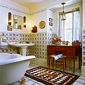 Nostalgic bathroom with antique washstand, pedestal washbasin, free-standing bathtub with gilt feet and blue and white wall tiles