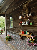 Wooden house with bench, flower arrangements and collection of bird boxes on roofed veranda,