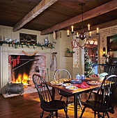 A dining room decorated for Christmas with a fire burning in the grate and a view of the Christmas tree