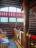 View from log cabin gallery to large, semicircular window; Native American woven rugs on balustrade, canoe hanging from ceiling