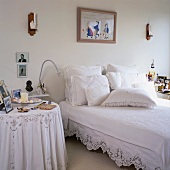 Lace-bordered vintage bedclothes and a variety of white scatter cushions on double bed