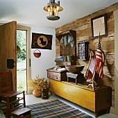 Diele mit einer rustikalen Holzwand im Blockhausstil mit einer langen Holztruhe und Antiquitäten aus der amerikanischen Gründerzeit