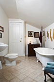 Renovated bathroom in attic with modern toilet and antique bathtub