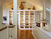 Attic room with white shelving holding large collection of model boats