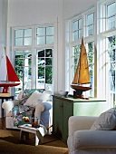 Maritime living room with model sailing boats, white armchairs and large windows