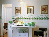Vintage-style kitchen with counter, bar stools and collection of Fire King mugs hanging on wall