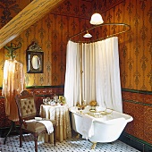 Free-standing bathtub with gilt feet and shower head and shower curtain hanging above in nostalgic bathroom