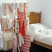 Antique bed behind red and white vintage bed linen hanging on a clothes horse