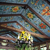 Wooden ceiling painted with Norwegian floral motifs and chandelier decorated with fresh flowers
