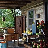 Rustikale Veranda eines Blockhauses mit geernteten Gartenfrüchten und einem Sommerblumenstrauss