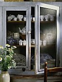 Vintage-style display cabinet with collection of blue and white crockery