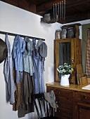 Antike Kleidungsstücke von 1850 hängen dekorativ in einer Küche mit Vintagemöbeln