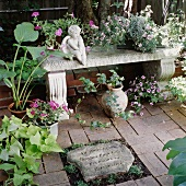 Decorative stone bench with planters and angel figurine