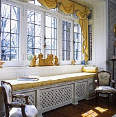 Large window in country house with golden yellow cushions on window seat and gilt ornaments on windowsill