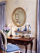 Antique escritoire below gilt-framed, oval mirror