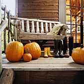 Old wooden bench on veranda behind large pumpkins and wellingtons