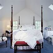 Grand bed with high bedposts and ottoman in attic bedroom