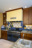 Modern fitted kitchen with wooden cupboards and patterns of yellow and blue wall tiles