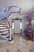 Elegant, pastel foyer with staircase
