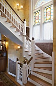 Grand staircase with ornate stained and leaded glass windows and carved wood panelling on walls