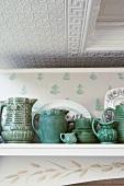 Green ceramics on shelf below stucco ceiling